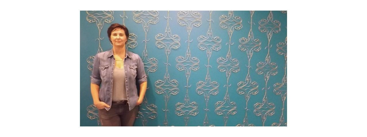 "Holly Ballard Martz and her wall installation, ""Danger of Nostalgia in Wallpaper Form (in utero)."""